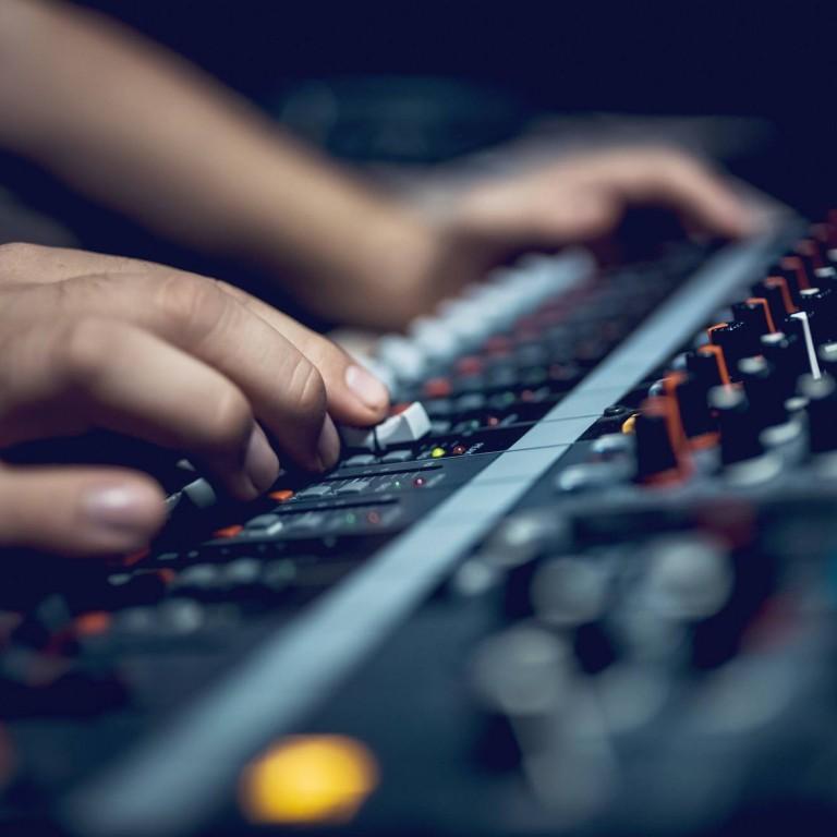 zoom sur une console audio des mains montent le son